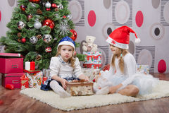 Girl opens gift sisters have a Christmas tree Royalty Free Stock Photography