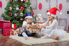 Girl opens gift sisters have a Christmas tree Stock Image