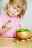 Girl opens peas Royalty Free Stock Image