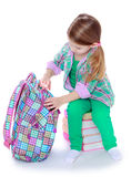 The girl opens a school backpack Royalty Free Stock Images