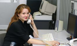 Girl operator in office. Business woman speaks over telephone Royalty Free Stock Photography