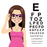 Girl At Ophthalmologist. Beautiful young girl with glasses reading sight test characters at ophthalmologist Stock Photo