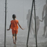 The girl in orange. Young girl walking in fountain stock photos