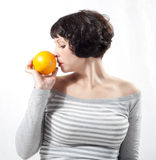 Girl with orange. Portrait of a young girl in profile with an orange in his hand. Isolated on white Stock Photos