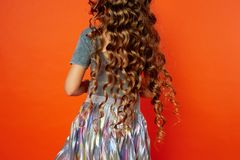 Girl on orange background in the Studio. Very long curly hair like in a fairy tale.Rapunzel. developing in the movement Royalty Free Stock Photography