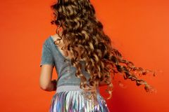 Girl on orange background in the Studio. Very long curly hair like in a fairy tale.Rapunzel. developing in the movement Royalty Free Stock Photo