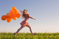 Girl with orange balloons outdoor Royalty Free Stock Photography