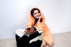 Girl in orange bathrobe reading magazine at home Stock Images