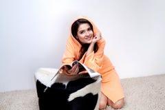 Girl in orange bathrobe reading magazine at home Stock Images