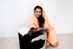 Girl in orange bathrobe reading magazine at home Stock Photo