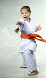 Girl with an orange belt beat blow arm Stock Photos