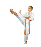 Girl with an orange belt beats mae-geri. On the white background stock photo
