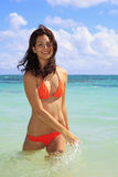 Girl in orange bikini in the water Stock Images