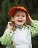Girl in orange cap. Child in orange cap play under tree Royalty Free Stock Photography