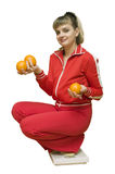 The Girl and an orange diet. The image of the girl sat down on floor scales and holding oranges Royalty Free Stock Photography