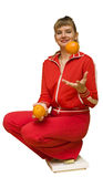The Girl and an orange diet. The image of the girl sat down on floor scales and holding oranges Stock Photo