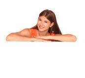 Girl in orange dress behind white board Royalty Free Stock Photos