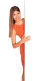 Girl in orange dress behind white board Stock Photos