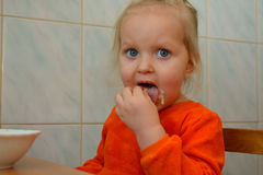 Girl in the orange dress eating Royalty Free Stock Images