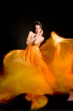 Girl in the orange dress from flying fabric Stock Photos