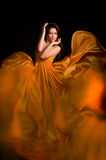 Girl in the orange dress from flying fabric Stock Images