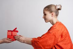 Girl in orange dress gets a gift Royalty Free Stock Photo