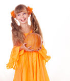 Girl in orange dress with pumpkin.  Thanksgiving. Royalty Free Stock Photo