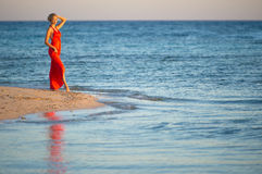 Girl in orange dress by seas edge 2 Stock Photos