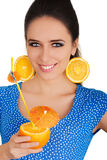 Girl with Orange Drink and Orange Slice Earrings White Background. Young woman with orange slice earrings holding a sliced orange with a straw on white Royalty Free Stock Photos