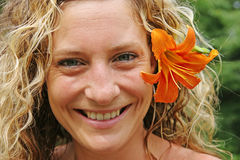 Girl with orange flower behind her ear Stock Image