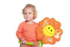 Girl with orange flower toy Stock Image