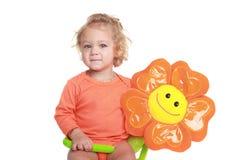 Girl with orange flower toy Stock Image