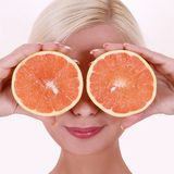 Girl with orange fruits isolated on white background, smiling blonde young woman Stock Images