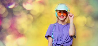 Girl with orange glasses and headphones Stock Image