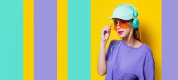 Girl with orange glasses and headphones Stock Images