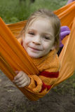 Girl in orange hammock in forest Stock Image