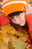 Girl in orange hat on leaves with sad face. Stock Photo
