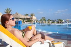 Girl with orange juice  at resort hotel Stock Photography