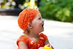 A girl in an orange knitted dress and hat is surprised, rejoices, screams, cries, raises her hands. children`s fashion stock photo