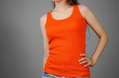 A girl in a orange plain t-shirt. Empty tank top. Closeup. Isola Royalty Free Stock Photos