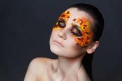 Girl with orange and red rhinestones on her face. Portrait of a girl with an original make-up. Beauty close-up. Orange and red rhinestones on a face Stock Photos