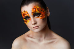 Girl with orange and red rhinestones on her face. Portrait of a girl with an original make-up. Beauty close-up. Orange and red rhinestones on a face Royalty Free Stock Photos