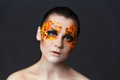 Girl with orange and red rhinestones on her face. Portrait of a girl with an original make-up. Beauty close-up. Orange and red rhinestones on a face Stock Photography