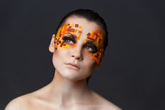 Girl with orange and red rhinestones on her face. Portrait of a girl with an original make-up. Beauty close-up. Orange and red rhinestones on a face Royalty Free Stock Images