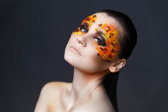 Girl with orange and red rhinestones on her face. Portrait of a girl with an original make-up. Beauty close-up. Orange and red rhinestones on a face Royalty Free Stock Photo