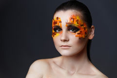 Girl with orange and red rhinestones on her face. Portrait of a girl with an original make-up. Beauty close-up. Orange and red rhinestones on a face Royalty Free Stock Photography