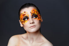 Girl with orange and red rhinestones on her face. Portrait of a girl with an original make-up. Beauty close-up. Orange and red rhinestones on a face Stock Image
