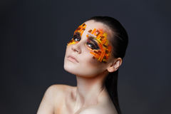 Girl with orange and red rhinestones on her face. Portrait of a girl with an original make-up. Beauty close-up. Orange and red rhinestones on a face Stock Photo