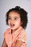 Girl in Orange Shirt. Close up of a young toddler girls brown eyes Stock Photo