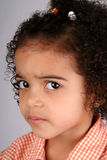 Girl in Orange Shirt. Close up of a young toddler girls brown eyes Royalty Free Stock Image